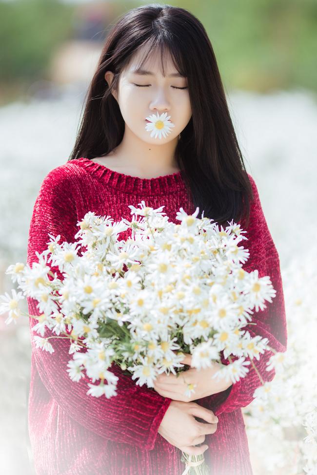Vẻ đẹp của thiếu nữ tuổi xuân hòa cùng vẻ đẹp của loài hoa nhỏ tạo nên hình ảnh say lòng người.