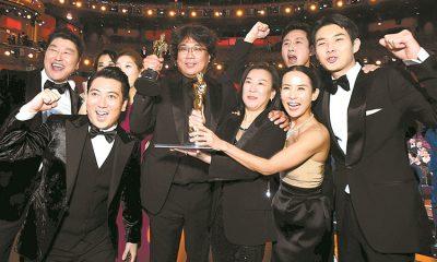Choi Woo Sik (phải) và êkíp Parasite trên sân khấu nhận giải Oscar. Ảnh: AFP.